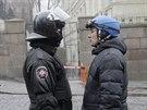 Dva světy. Policejní těžkooděnec a protivládní demonstrant v lyžařské přilbě.