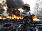 Plynová maska a hořící pneumatiky na jedné z barikád (21. února 2014)
