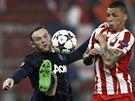 Wayne Rooney z Manchesteru (vlevo) se snaží odehrát míč před José Holebasem z...