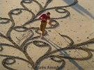 Andres Amador tvoří obrazy na pláži.