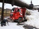 Sněží? To opravdu ne. Náklaďák vyklápí z vlečky umělý sníh vyrobený ve ski