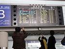 Lidé na letišti v Pekingu si fotí informační tabuli s údaji o problémech...