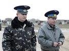Ukrajinští důstojníci odchází od ruských vojáků, kteří okupují letiště v...