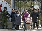 Příbuzní ukrajinských vojáků (v pozadí) stojí před bránou areálu v Perevalném,...