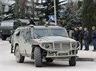 Ozbrojený voják vyhlíží z ruského armádního vozidla v Krymské Balaklavě.