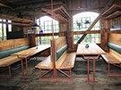 Interiér lokálu s repasovanými, litinovými okny z bouraček. Sedí se na lavicích
