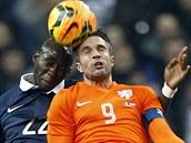 Nizozemský útočník Robin Van Persie v souboji s Eliaquim Mangalou z Francie v...