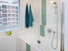 Koupelnu v b�l� barv� o�ivuj� svisl� pruhy zelen� mozaiky.