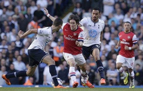 V SEVŘENÍ. Tomáš Rosický z Arsenalu si hraje s protihráči z Tottenhamu. Ti ho