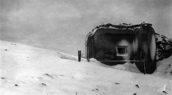 Německé jednotky na svém postupu míjí zasněžené pevnůstky vnitrozemských linií lehkého opevnění, jako např. zde u Velešína v jižních Čechách. Sněhem zaváté střílny řopíků však mlčí. Stejně jako v říjnu 1938.