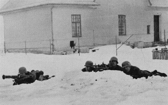Německý postup je prováděn za plného bojového jištění. Na snímku obsluha německého kulometu MG 34 v palebném postavení. Vojáci jsou vybaveni také dálkoměrem.