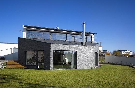Obývací prostor má díky svému umístění v zahradě a velkým proskleným plochám