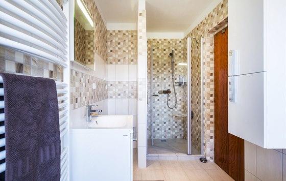 Sprchový kout má rozměry přibližně 100 × 100 cm, dveře ke sprchovému koutu z