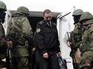 Maskovan� ozbrojenci vyv�d� d�stojn�ka ze s�dla ukrajinsk�ho n�mo�nictva v...