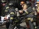 Hasiči vynášejí zraněné ze zřícené budovy v newyorské čtvrti Harlem (12. března...