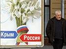 Muž prochází v Simferopolu kolem plakátu s nápisy Krym a Rusko. (12. března...