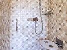 Sklopné sedátko a svislé madlo zvyšují bezpečnost ve sprchovém koutu.