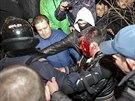Policisté odvádějí muže zraněného při potyčkách v Doněcku (13. března 2014).