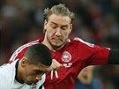 Dánský útočník Nicklas Bendtner (v červeném) svádí během přípravného utkání souboj s Chrisem Smallingem z Anglie.