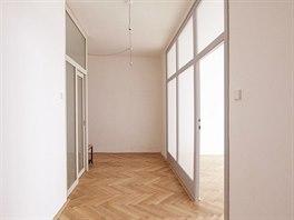 Prostornou vstupní halu bytu osvětluje denní světlo přes prosklenou stěnu ložnice.