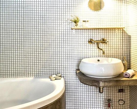 Do koupelny zvolila majitelka mozaiku, beton a retro baterie.