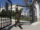 Ukrajinský voják zavírá bránu do vojenské základny v krymském městě Belbeku...