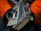 Záchranář drží zablácenou bibli, kterou našel na místě sesuvu půdy v americkém...
