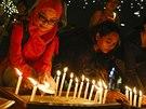 Lidé v centru Kuala Lumpur zapalují svíčky k uctění památky cestujících letu...