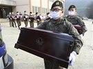 Jihkorejští vojáci nakládají na hřbitově Padžu rakve s ostatky čínských vojáků