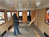 Jaromír Foltýn v renovovaném vagonu ukazuje, kde bude výčep a kde kamna.