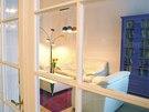Průhled do obývacího pokoje s modrou knihovnou