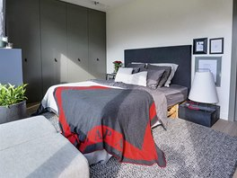 Velká postel je sestavená z palet, doplněná o čalouněná záda a kvalitní vysoké