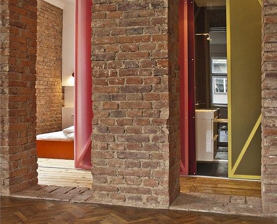 Surové obnažené cihelné zdivo a nosné konstrukce překladů vnášejí do bytu lehký