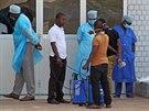 Zam�stnanci nemocnice v guinejsk� metropoli Conakry p�ij�maj� pacienta s...