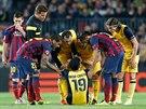 Hráči Barcelony a Atlétika Madrid (ve žlutém) se sklánějí nad zraněným Diegem...