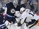 Brankář Ondřej Pavelec z Winnipegu bojuje u mantinelu s  Taylorem Pyattem z...