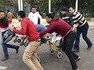 Kolemjdoucí civilisté pomáhají záchranáři odvézt muže, jehož v Káhiře zranil
