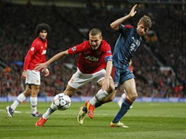 Obránce Nemanja Vidič z Manchesteru United se snaží zpracovat míč před Thomasem...