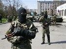 Neozna�en� ozbrojenci v centru Slavjansku. Na jejich transport�rech je vid�t...