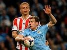 Edin Džeko (v modrém) z Manchesteru City je faulován Wesem Brownem ze...