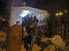 Muž se zahřívá u ohně poblíž barikád před budovou tajné služby v Luhansku. (13....