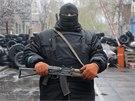 Proruský ozbrojenec stojí na stráži před obsazenou policejní stanicí ve