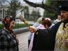 Duchovní ve východoukrajinském Slavjansku na Bílou sobotu kropí věřící svěcenou...