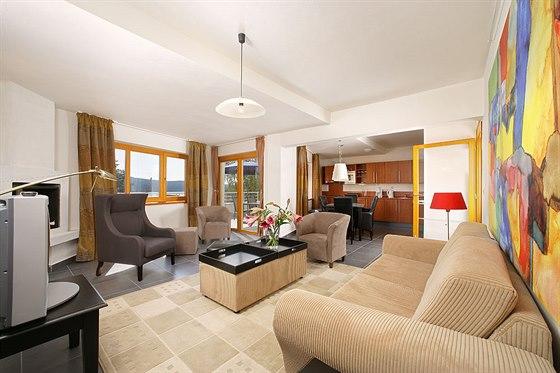 Prostorný obývací pokoj s krbem a velkou jižní terasou s výhledem na jezero