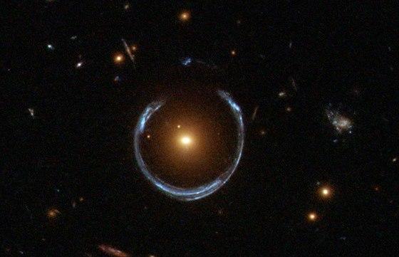 Snímek vzdálené modré galaxie zesílené (na snímku žlutou) galaxií LRG 3-757 v...