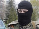 Maskovaný ozbrojený strážce s připnutou oranžovo-černou stuhou, která se stala...