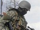 Maskovaný ozbrojený strážce s oranžovo-černou stuhou připnutou na uniformě.