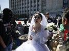 Nevěsta prochází okolo maskovaných ozbrojenců před okupovanou budovou...