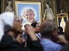 Věřící se modlí v jednom z vatikánských svatostánků vedle portrétu bývalého...