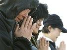 Příbuzní obětí z potopeného trajektu jihokorejské společnosti Sewol se modlí v